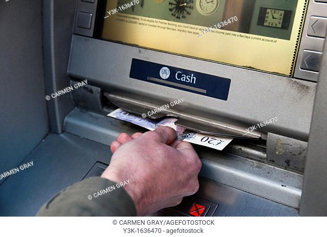 Detail of a hand withdrawing money from a cash machine