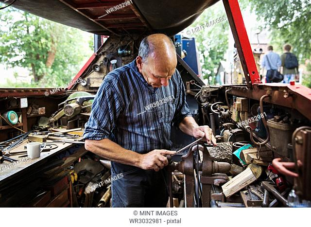 Blacksmith standing in his workshop, a floating forge on a narrowboat barge, working on a metal object, using a file