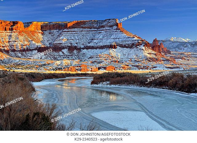 Red rock formations and Colorado River with snow in winter near sunset, Colordao Riverway Recreation Area, Utah, USA