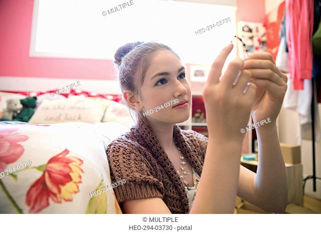 Girl making and examining jewelry in bedroom