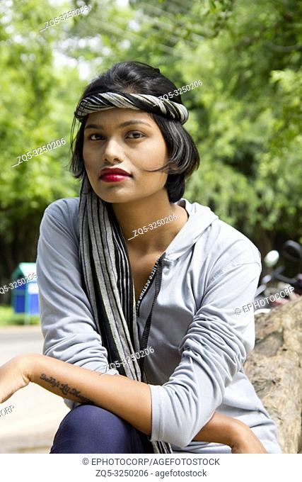 Young Indian girl with short hair wearing headgear and posing for camera, Pune