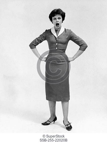Mid adult woman standing with arms akimbo and shouting