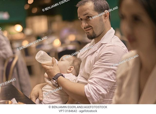 father giving his baby the bottle, feeding, Vegan Oriental, Kismet, in Munich, Germany