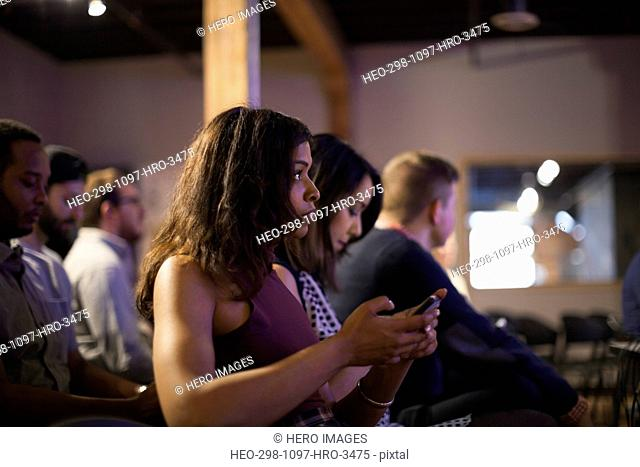 Woman in audience checking cell phone