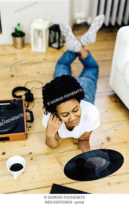 Young woman at home listening vinyl records, lying on ground