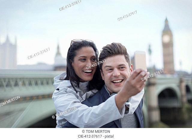 Playful, affectionate couple tourists taking selfie with camera phone in front of Westminster Bridge, London, UK