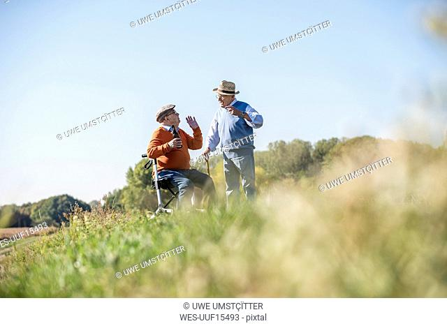 Old friends taking a stroll in the fields with walking stick and wheeled walker, talking about old times