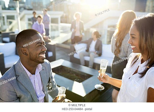 Smiling business people drinking champagne on sunny rooftop