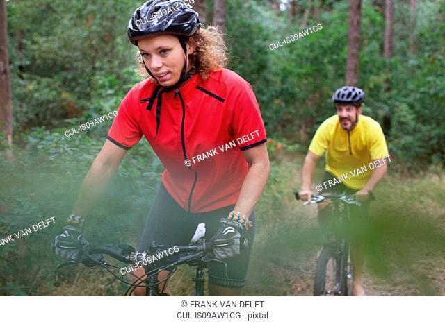 Mountain biking couple biking through forest