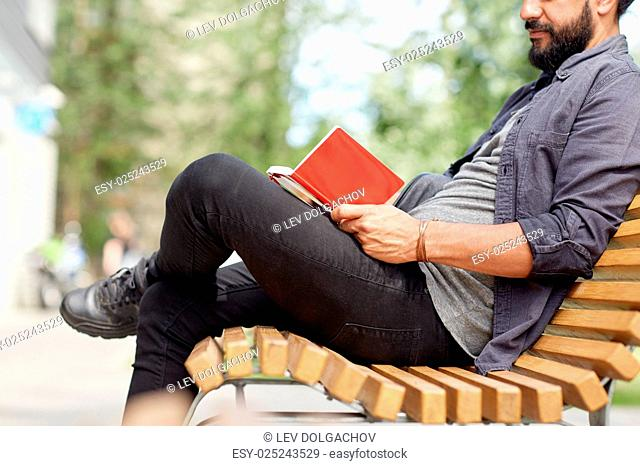 lifestyle, freelance, inspiration and people concept - close up of man writing to notebook or diary sitting on city street bench