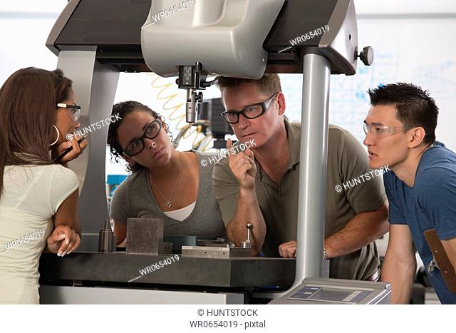 Engineering professor demonstrating a coordinate measuring machine to students