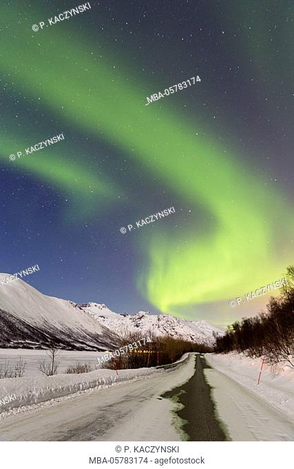 Aurora borealis over a snow-covered street in wintry mountain landscape, Tromsö, Troms, Norway, North Norway, North Scandinavia