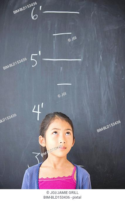 Vietnamese student standing under height markers on chalkboard