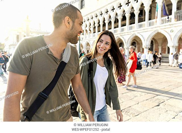 Italy, Venice, happy tourist couple enjoying the city at sunset