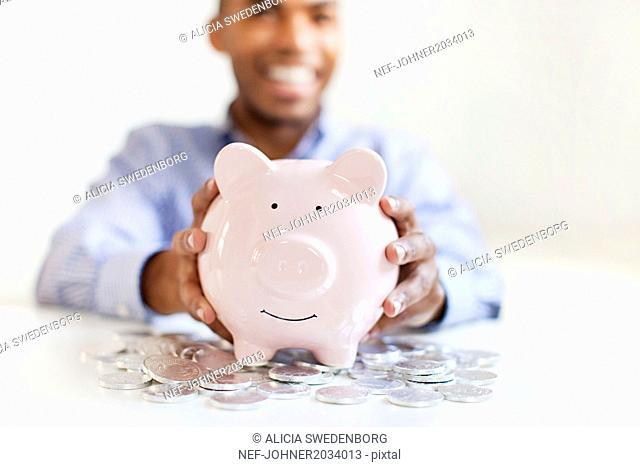 Young man putting coin in piggybank