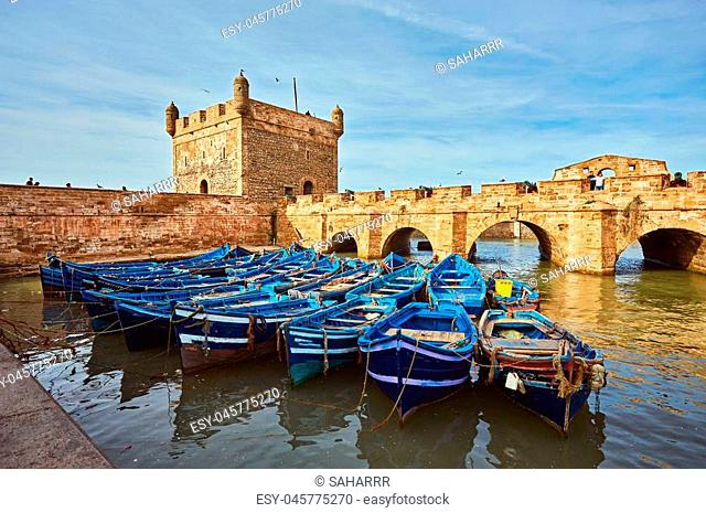 Fort of Essaouira in Morocco on a sunny day with blue boats on the water and selective focus
