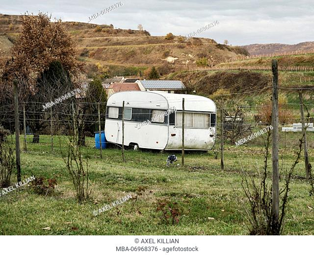 old caravan in a meadow, vineyards with vines in the background in autumn