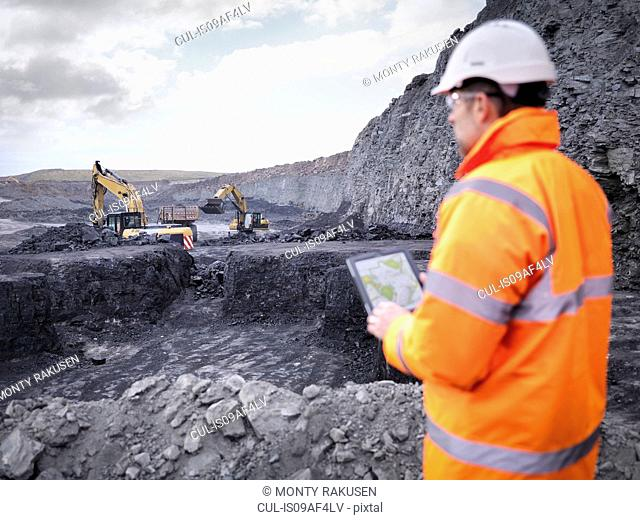 Miner checks plans on digital tablet in surface coal mine