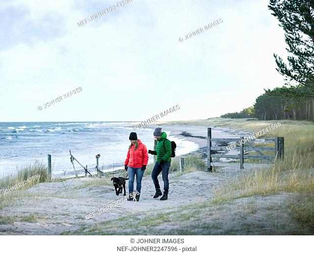 Couple with dog walking at sea