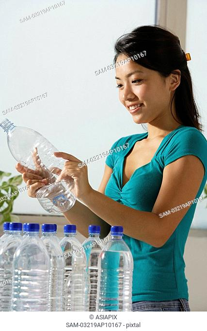 Young Asian woman recycling water bottles