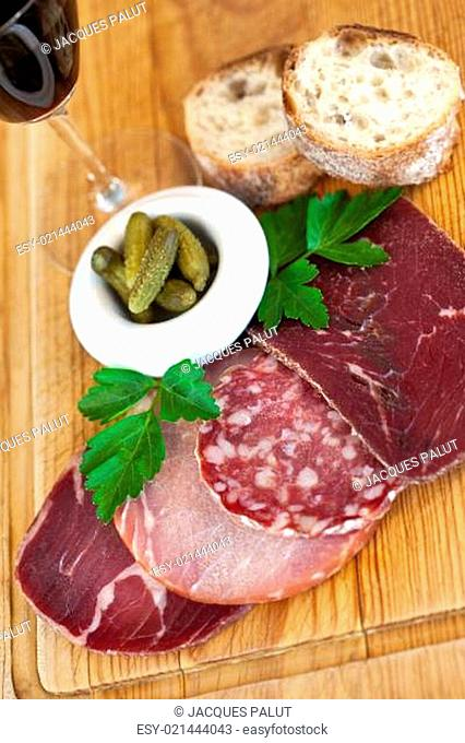 Ham, sausage and bread on a wooden board