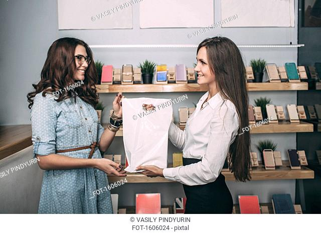 Young saleswoman handing over plastic bag to female customer in store