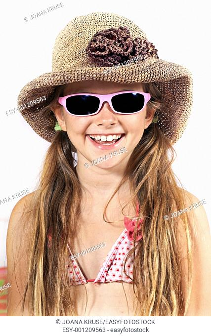 eight year old girl with hat, sunglasses and beach towel