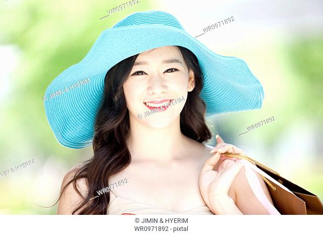 close up shot of a smiling woman in turquoise hat holding shopping bags