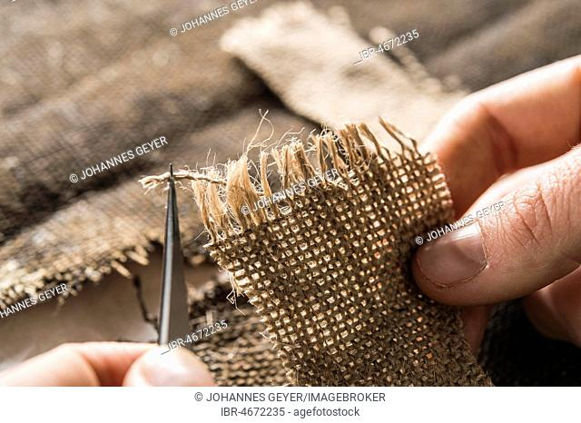 Restoration atelier,hand processing linen patch with thread bridges over crack in lent scarf, Munich, Bavaria, Germany