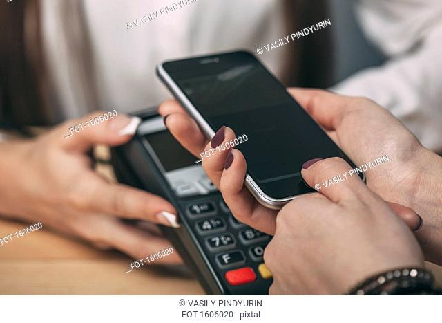 Detail image of woman using smart phone to pay at counter