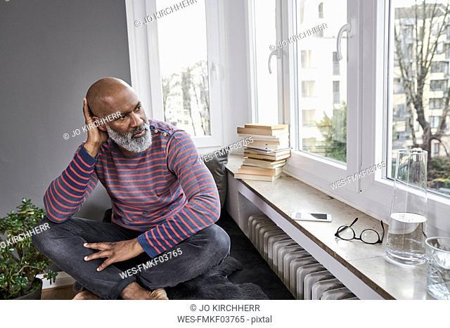 Mature man sitting cross-legged at the window