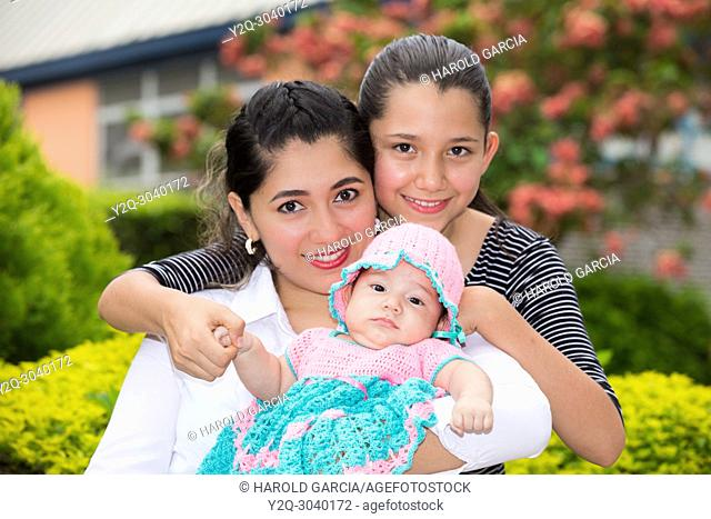 little baby in mom's arms and with big sister posing for the camera