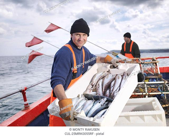 Fishermen on boat with catch of fish