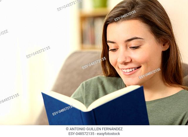 Teen reading a paper book sitting on a couch in the living room at home