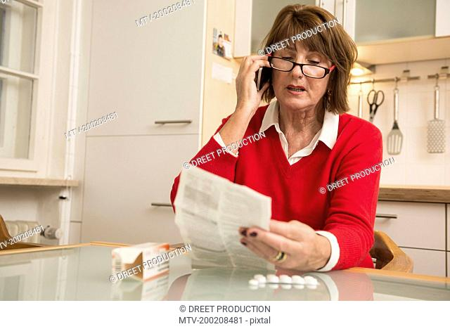 Senior woman reading package insert for pills and talking on phone, Munich, Bavaria, Germany