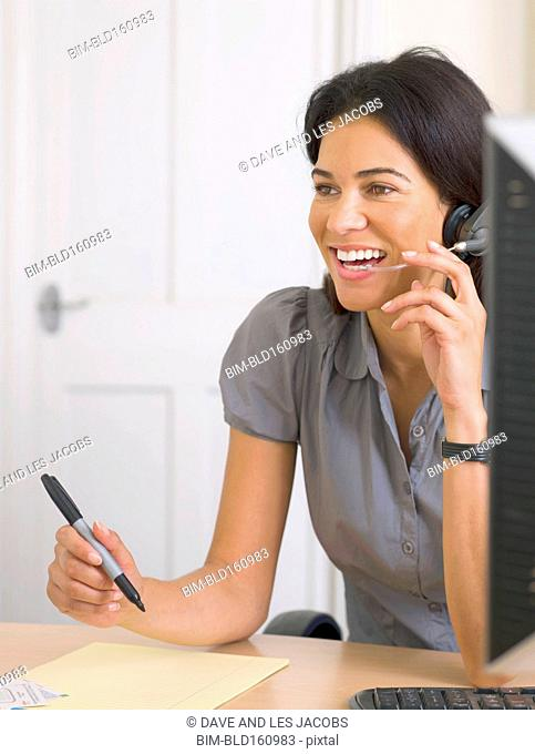 Mixed race businesswoman talking on headset at desk in office