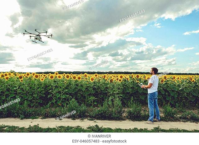 Professional agriculture drone flying with blue sky background controlled by young man. Octocopter flights outdoors, sunflower field