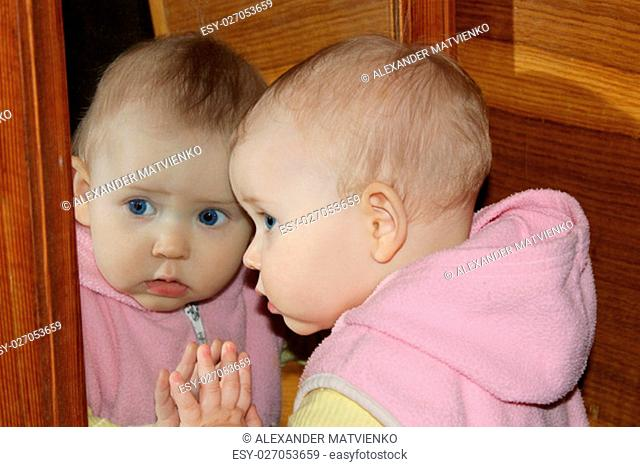 amusing baby looks at herself in front of mirror