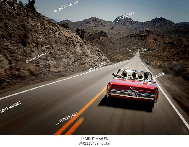 A red convertible car with five young people on a road trip. The open road
