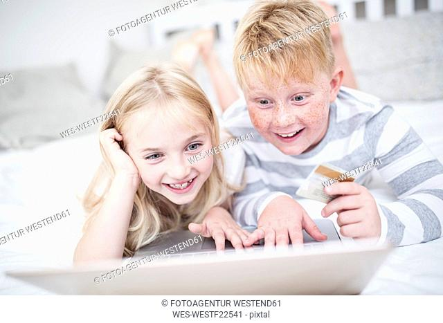 Brother and sister lying in bed holding credit card and using laptop