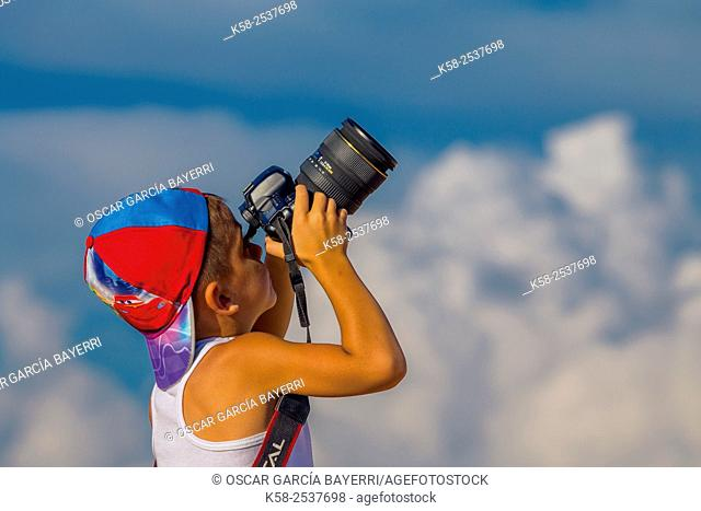 Child between 4 and 6 years working as a photographer and photographed the clouds on top of Lleida Montsec, Catalonia, region of Noguera