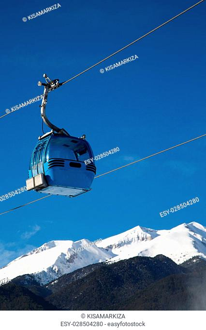 Cable car cabin and snow peaks of the mountains view