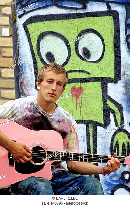 Teenager Playing Pink Guitar next to Graffiti, Winnipeg, Manitoba