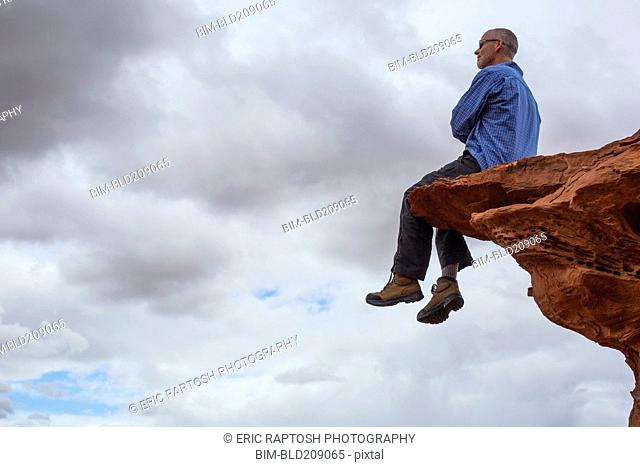 Caucasian man sitting on cliff edge