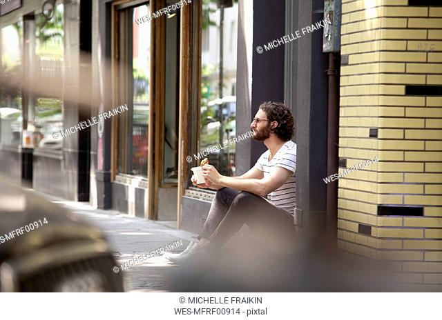 Young man with coffee mug and croissant sitting at entrance of a coffee shop