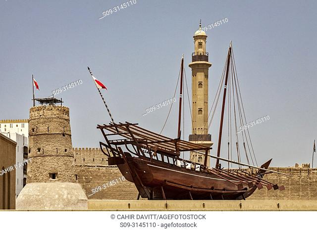 Traditional dhow ship exhibit in the Traditional Architecture Museum (Diwan) and the Minaret of the Bur Dubai Grand Mosque in the background, Bastakiya Quarter