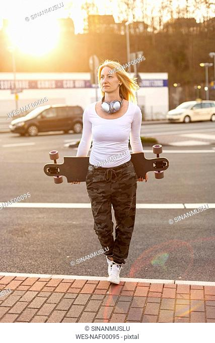 Portrait of blond woman with headphones and longboard