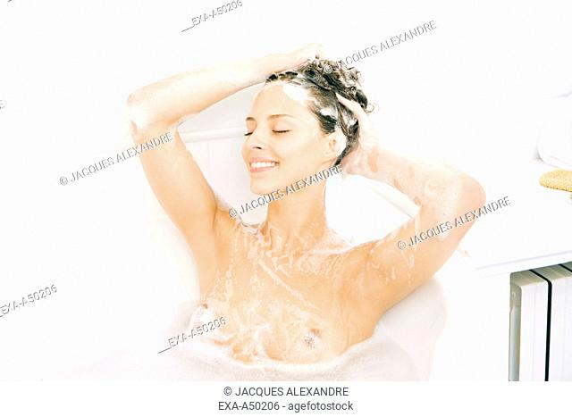 Young woman washing her hair in the bathtub after getting up in the morning