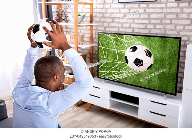 African Young Man Throwing Football On Television At Home