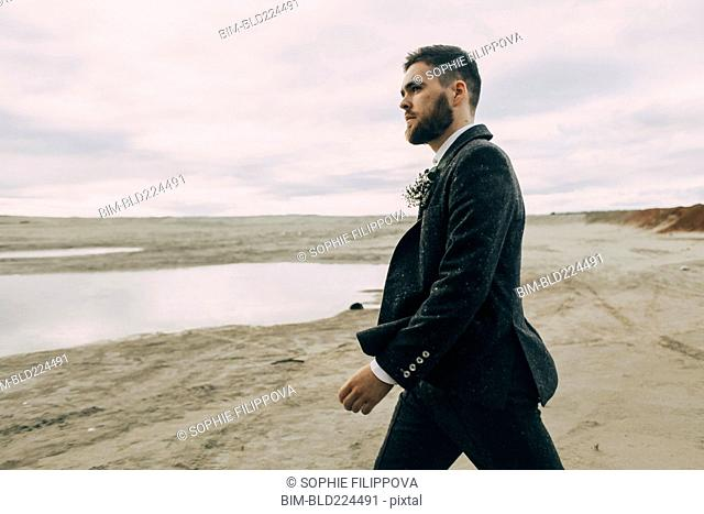 Caucasian groom walking on beach